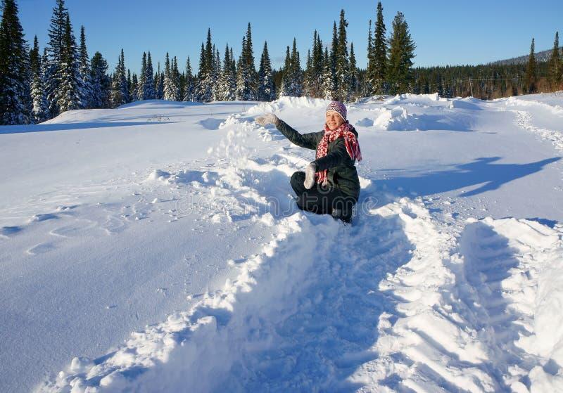 Mujer que juega con nieve para arriba por una tarde soleada. imagenes de archivo