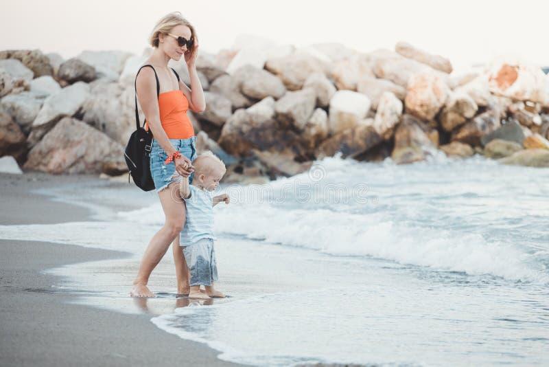 Mujer que juega con su beb? afuera El concepto de una vida familiar hecha y derecha feliz foto de archivo libre de regalías