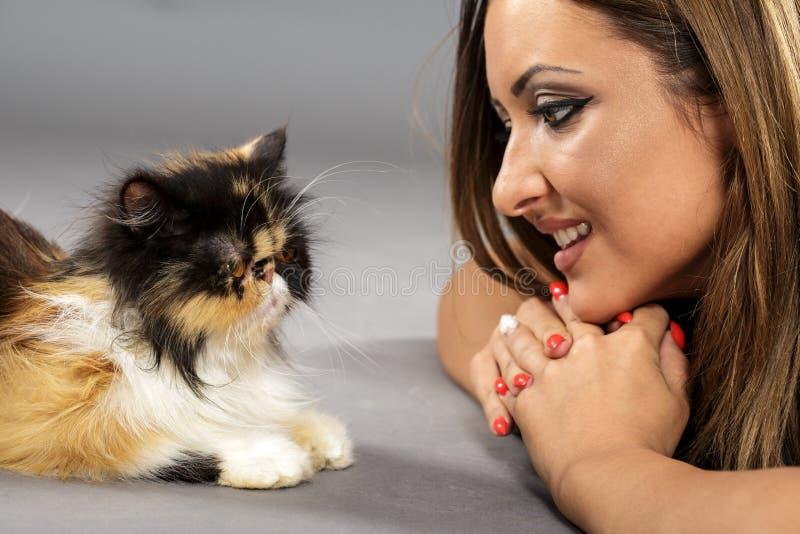 Mujer que juega con su gato fotos de archivo
