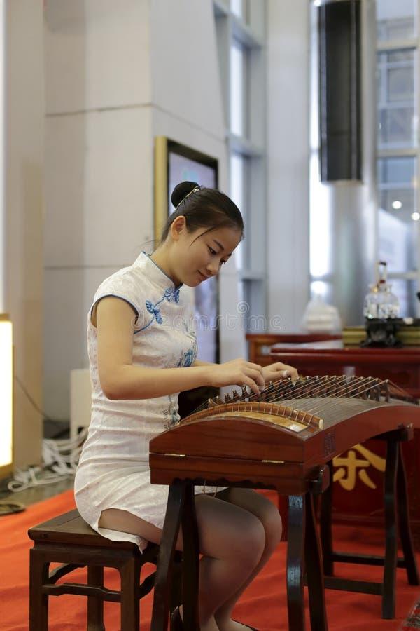 Mujer que juega el guqin chino imagen de archivo