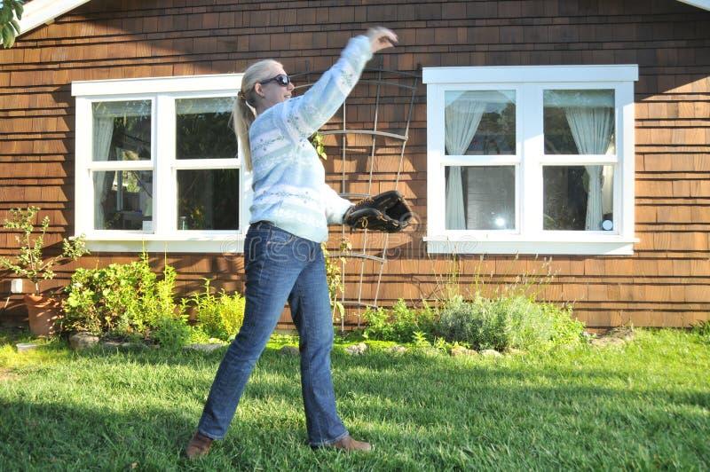 Mujer que juega el retén del béisbol en el patio trasero imagenes de archivo
