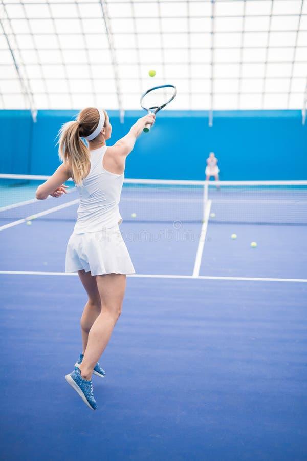 Mujer que juega el tiro de la acción del tenis imagen de archivo libre de regalías
