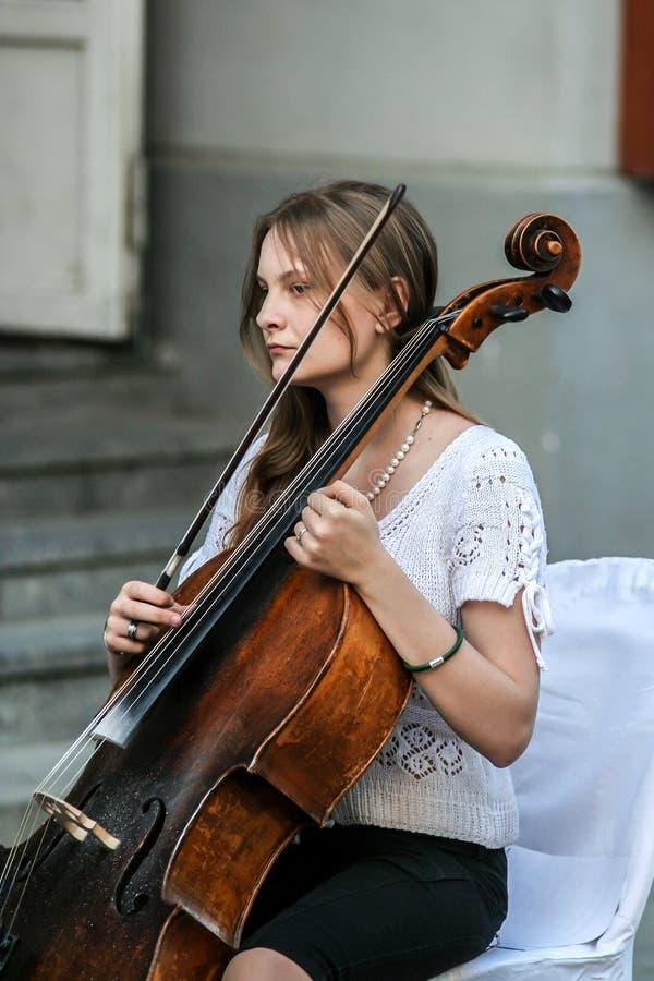 Mujer que juega en la calle, vista lateral del violoncelista fotos de archivo libres de regalías