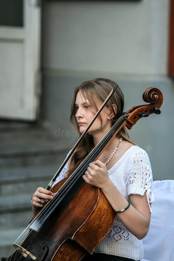 Mujer que juega en la calle, vista lateral del violoncelista fotos de archivo