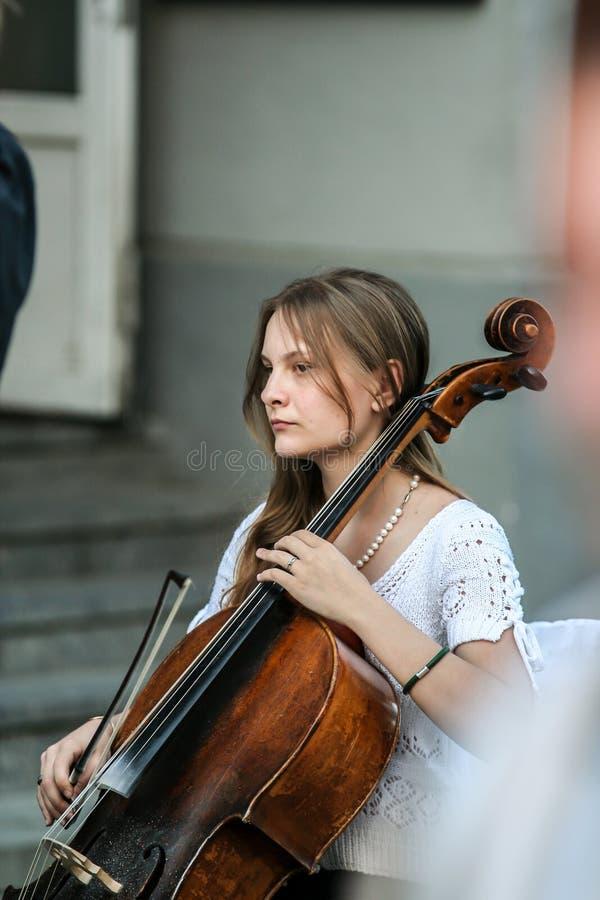 Mujer que juega en la calle, vista lateral del violoncelista imagen de archivo