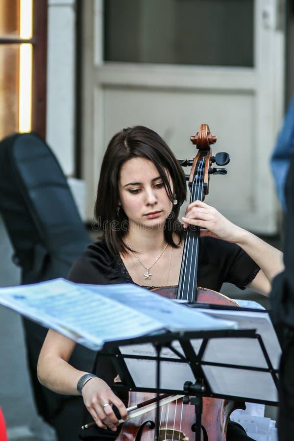Mujer que juega en la calle, vista lateral del violoncelista imágenes de archivo libres de regalías