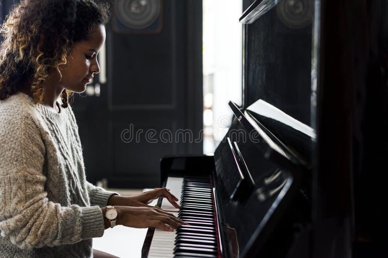 Mujer que juega en un piano foto de archivo libre de regalías
