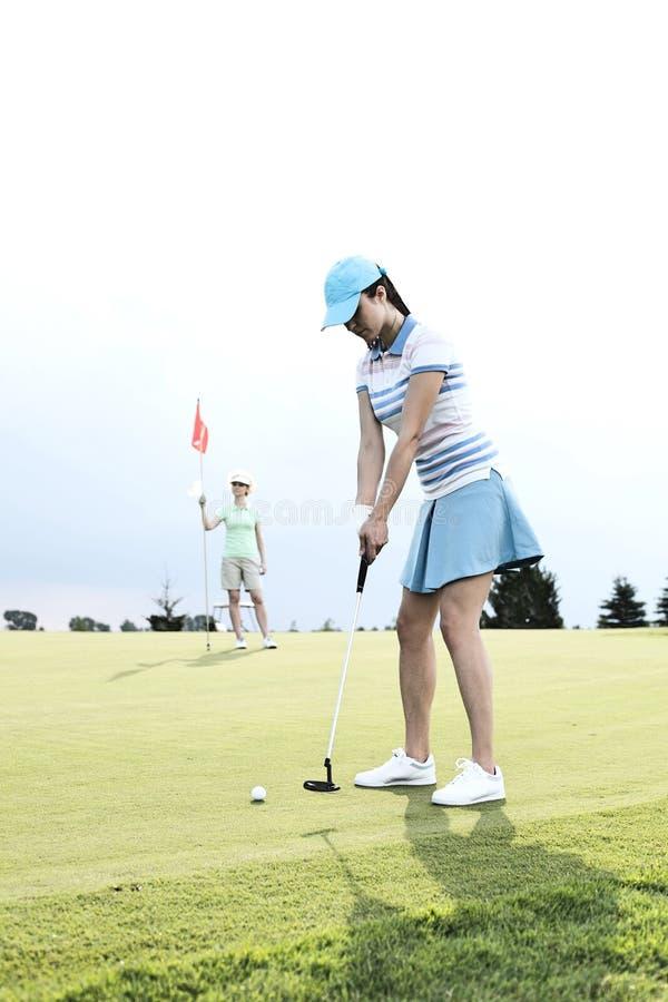 Mujer que juega a golf con el amigo femenino que sostiene la bandera contra el cielo imagenes de archivo
