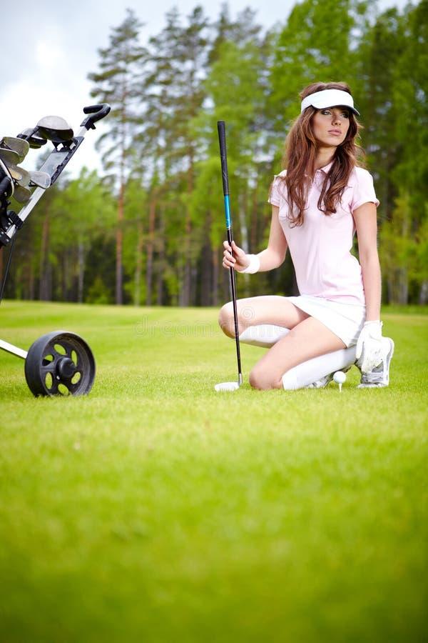Mujer que juega a golf en una mujer verde imagen de archivo