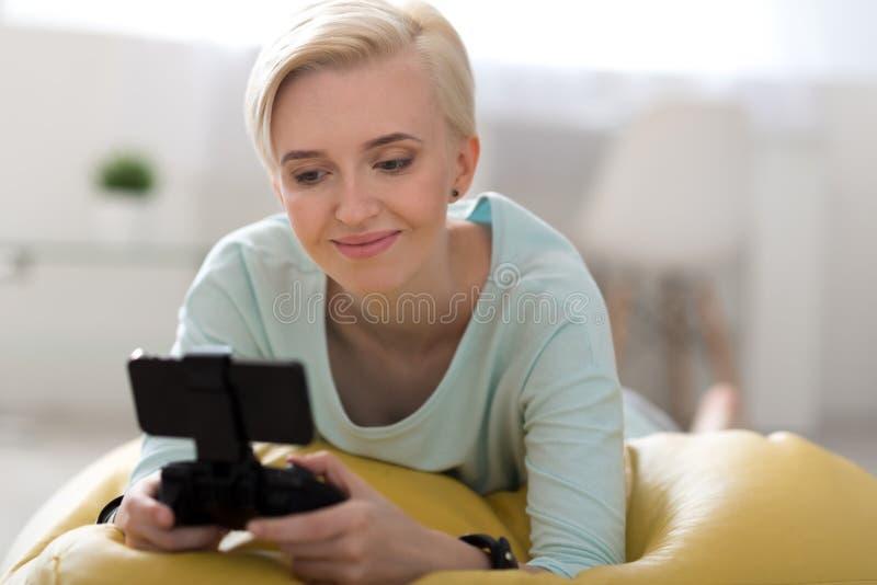 Mujer que juega a juegos en el smartphone fotos de archivo libres de regalías