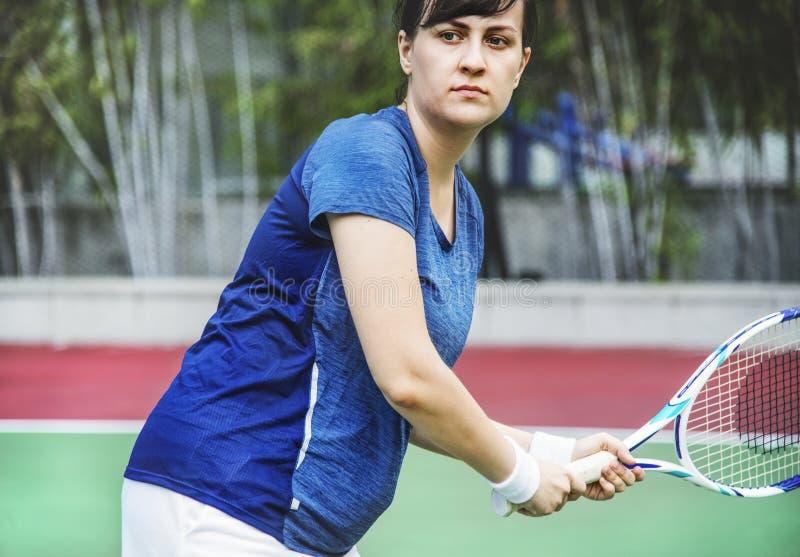 Mujer que juega a tenis en la corte imagenes de archivo