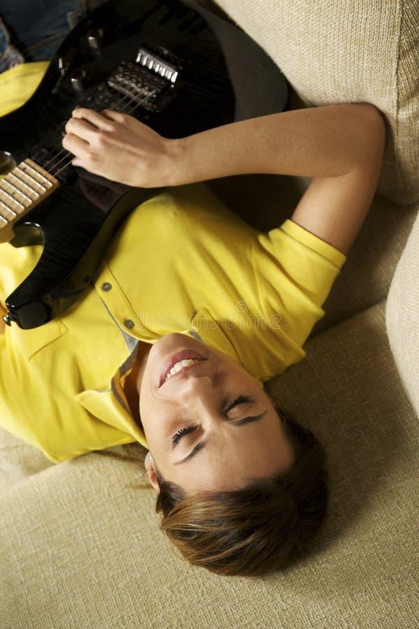 Mujer que juega y que entrena con la guitarra eléctrica en casa foto de archivo