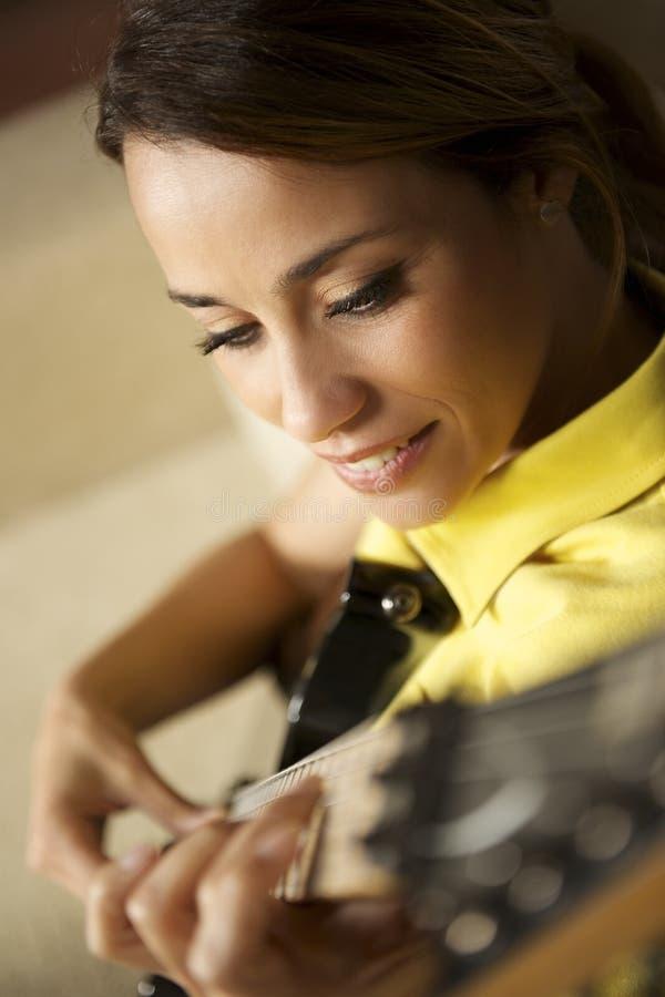Mujer que juega y que entrena con la guitarra eléctrica en casa fotografía de archivo