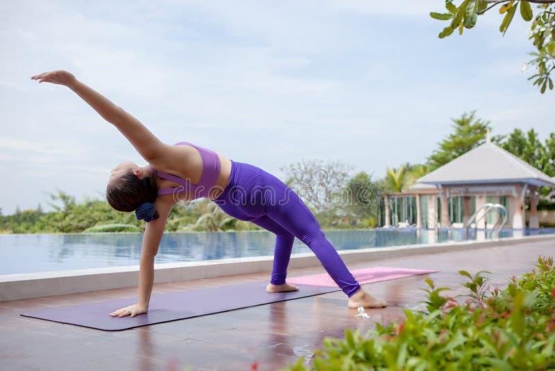 Mujer que juega a yoga sana al lado de la piscina de agua al aire libre de la natación imagen de archivo libre de regalías