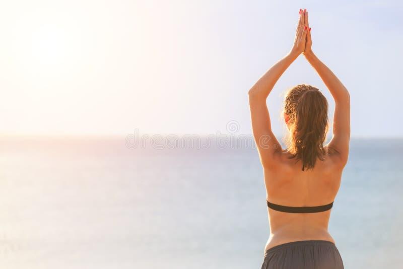 Mujer que juega yoga y ejercicio en la playa tropical en puesta del sol imagen de archivo