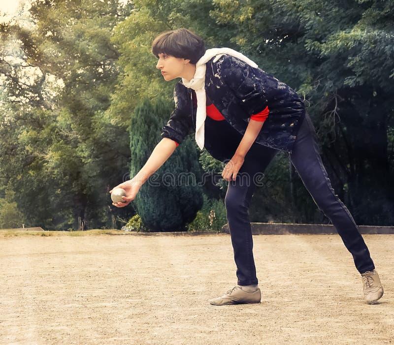 Mujer que lanza una bola del petanque en parque del th el días de fiesta fotografía de archivo
