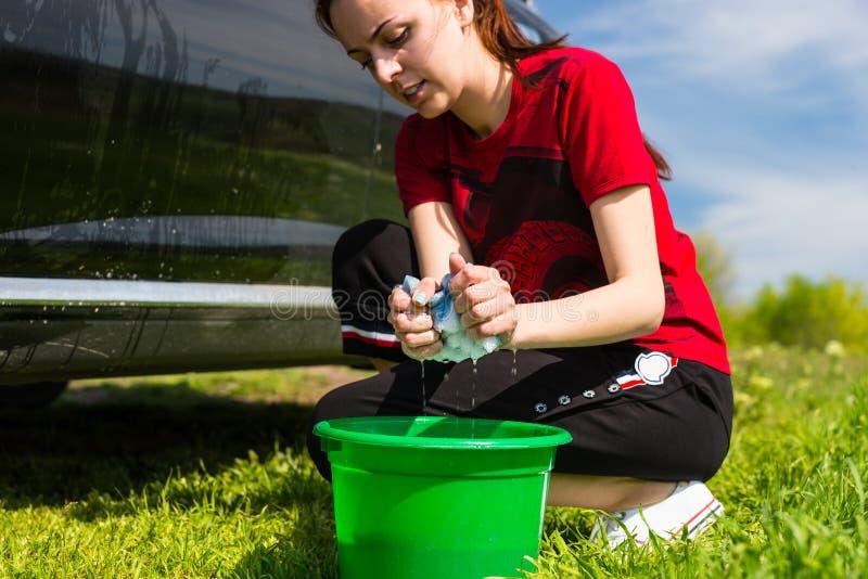 Mujer que lava el coche negro en campo con la esponja jabonosa foto de archivo libre de regalías