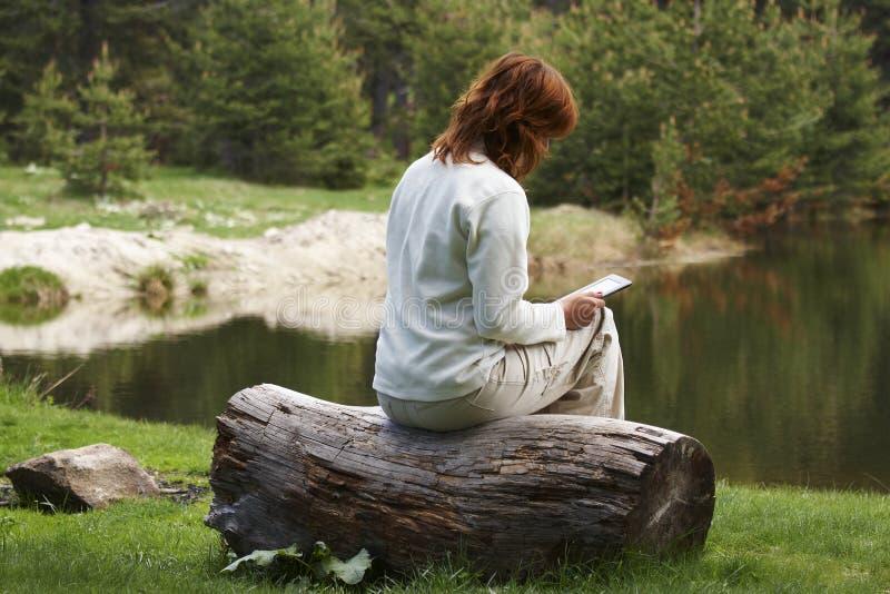 Mujer que lee el libro digital imágenes de archivo libres de regalías