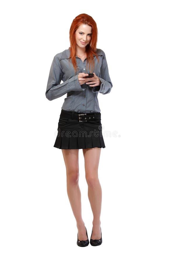 Mujer que lee el mensaje corto en su teléfono celular fotos de archivo