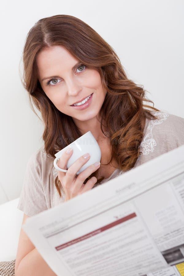 Mujer que lee el periódico imagen de archivo
