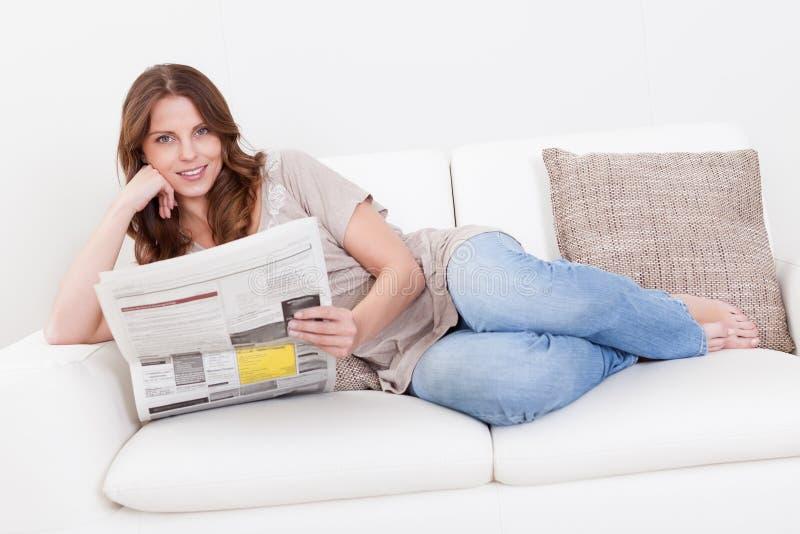 Mujer que lee el periódico imagenes de archivo