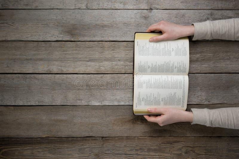 Mujer que lee la biblia en la oscuridad fotografía de archivo