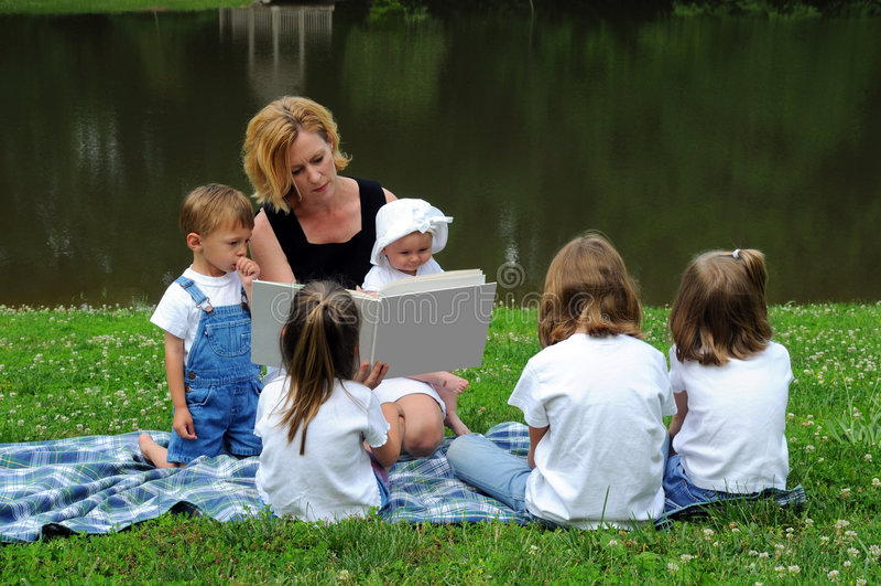 Mujer que lee a los niños imagen de archivo