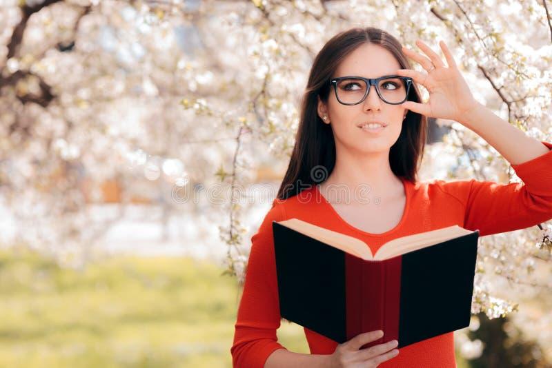 Mujer que lee un libro debajo de un árbol floreciente fotografía de archivo