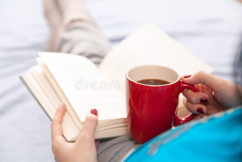 Mujer que lee un libro en cama imagenes de archivo
