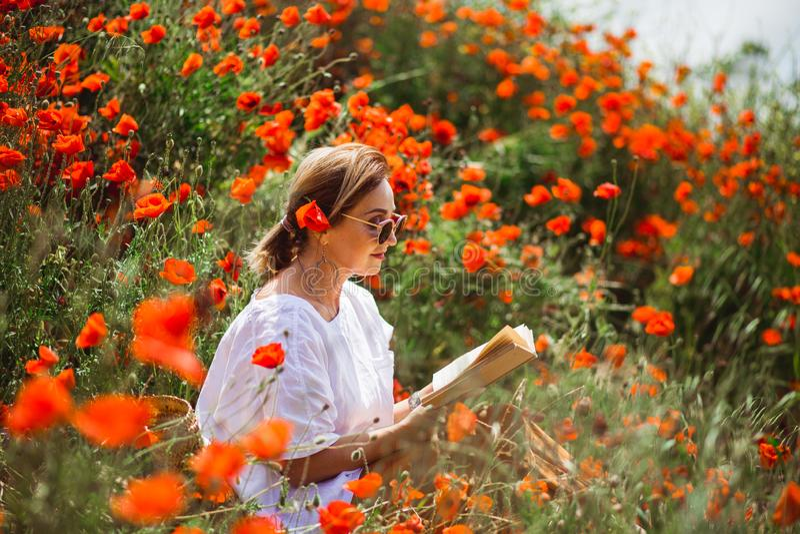 Mujer que lee un libro en un campo de amapolas rojas en humor de las flores de la primavera imágenes de archivo libres de regalías