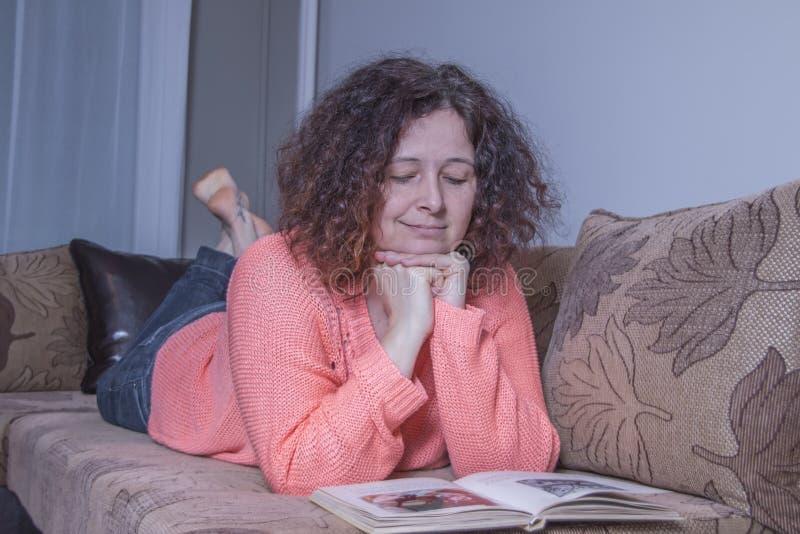 Mujer que lee un libro en la cama imagen de archivo libre de regalías