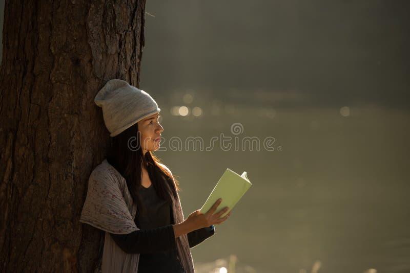 Mujer que lee un libro en la naturaleza imagen de archivo