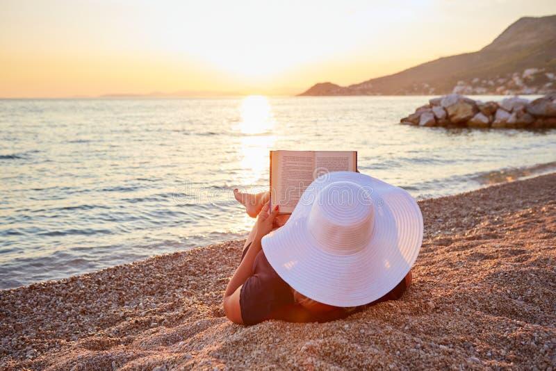 Mujer que lee un libro en la playa fotos de archivo