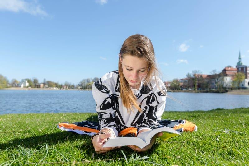 Mujer que lee un libro en una posición de mentira fotos de archivo