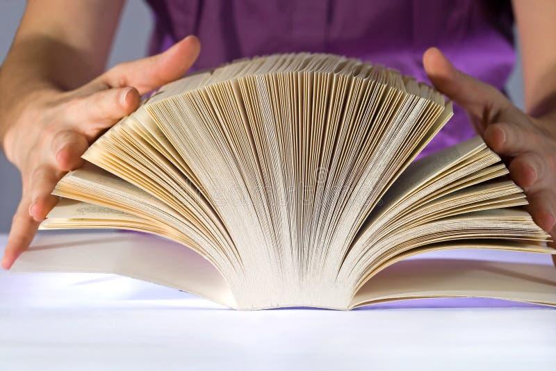 Mujer que lee un libro grueso fotos de archivo