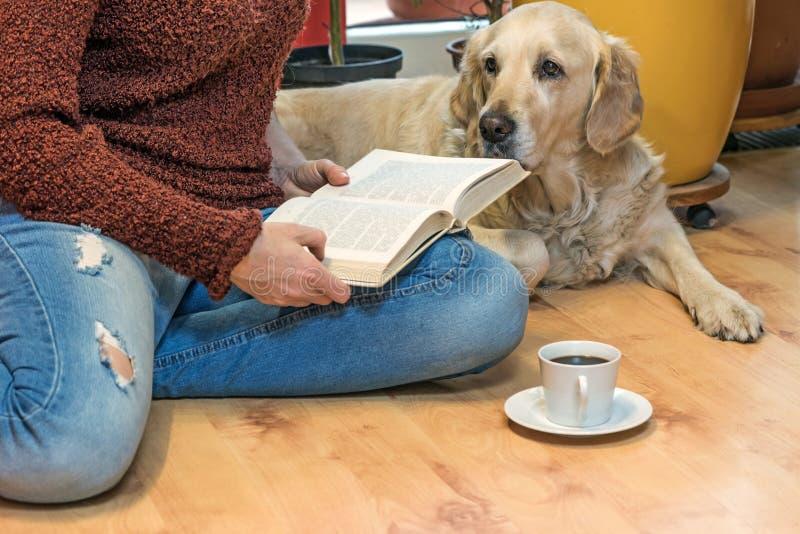 Mujer que lee un libro que se sienta en el piso imagenes de archivo