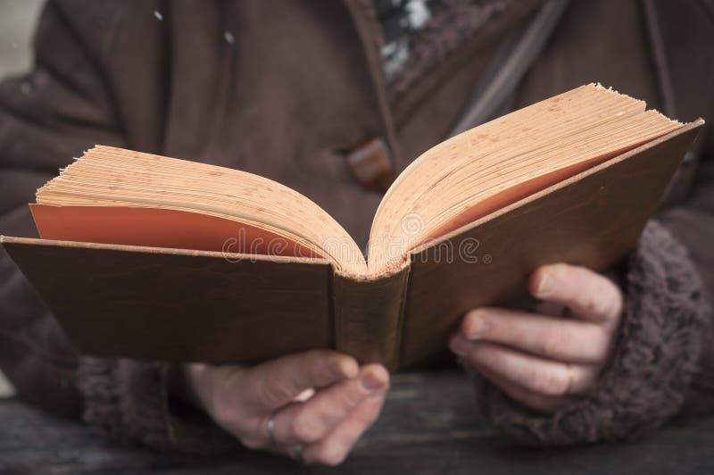 Mujer que lee un libro viejo en al aire libre imagenes de archivo