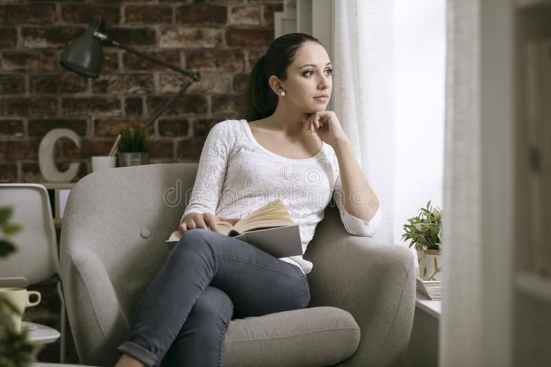 Mujer que lee un libro y que mira lejos imagenes de archivo