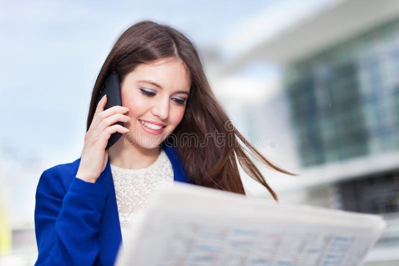 Mujer que lee un periódico imagenes de archivo