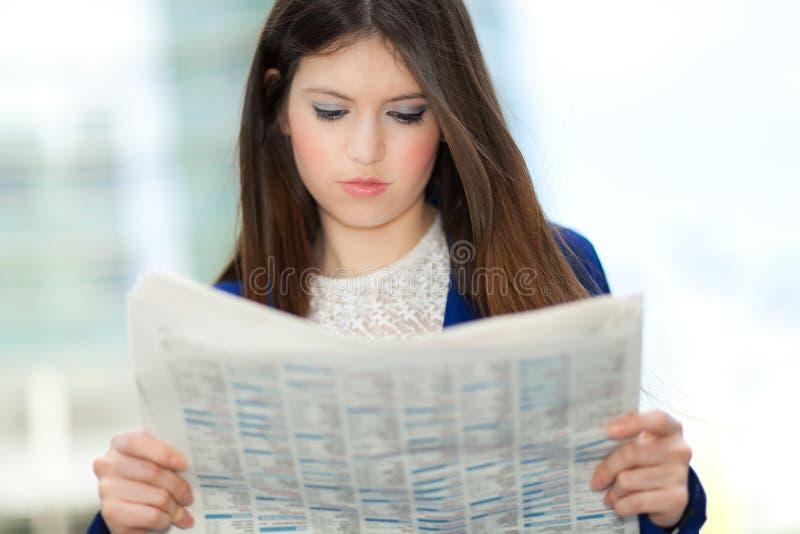 Mujer que lee un periódico imágenes de archivo libres de regalías