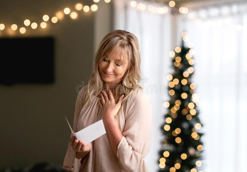 Mujer que lee una nota o una tarjeta sentida del mensaje fotografía de archivo libre de regalías