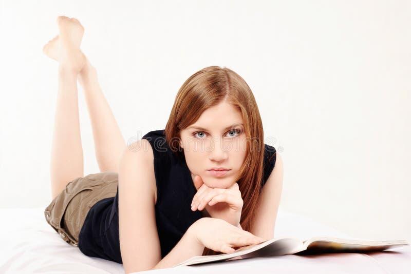 Mujer que lee una revista imágenes de archivo libres de regalías