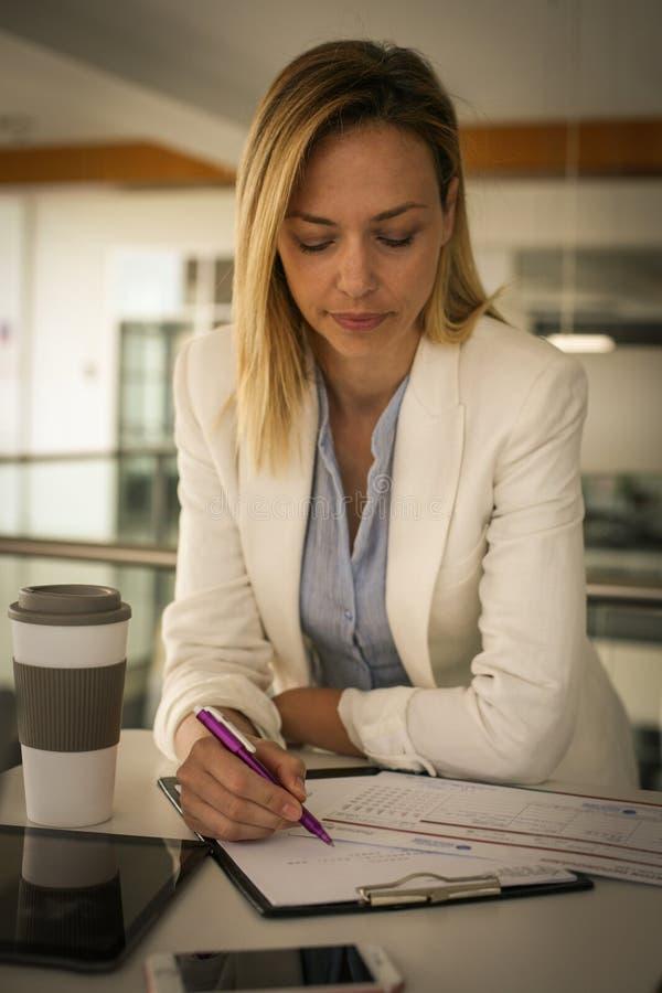 Mujer que lee y que firma el contrato en la oficina S foto de archivo