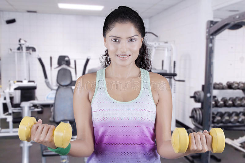 Mujer que levanta dos pesas de gimnasia en el centro de aptitud imágenes de archivo libres de regalías