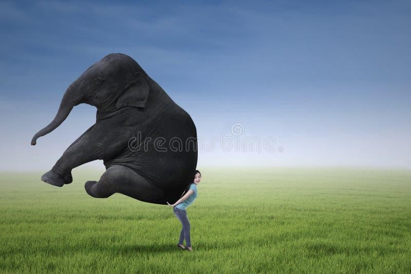 Mujer que levanta el elefante pesado imágenes de archivo libres de regalías