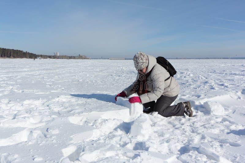 Mujer que levanta un bloque de la nieve para construir un iglú imagen de archivo libre de regalías