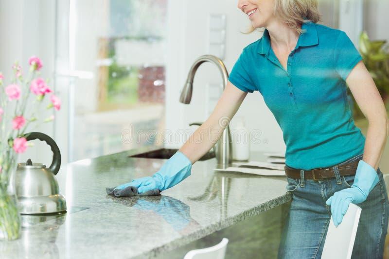 Mujer que limpia abajo de encimera de la cocina imagen de archivo