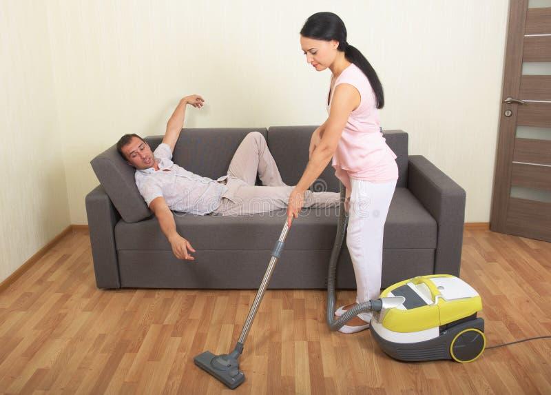 Mujer que limpia con la aspiradora y hombre de reclinación fotos de archivo