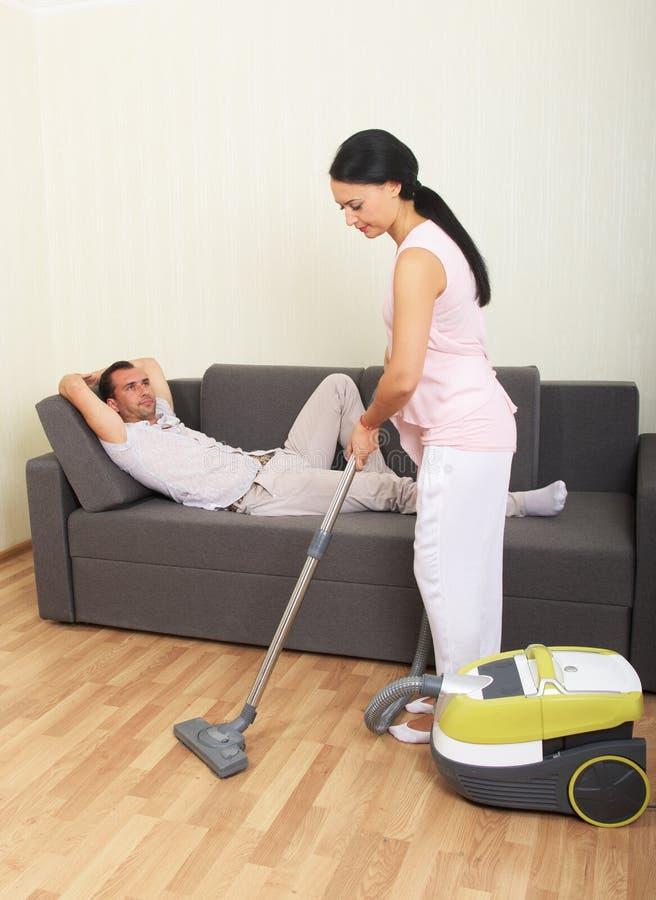 Mujer que limpia con la aspiradora y hombre de reclinación fotografía de archivo libre de regalías