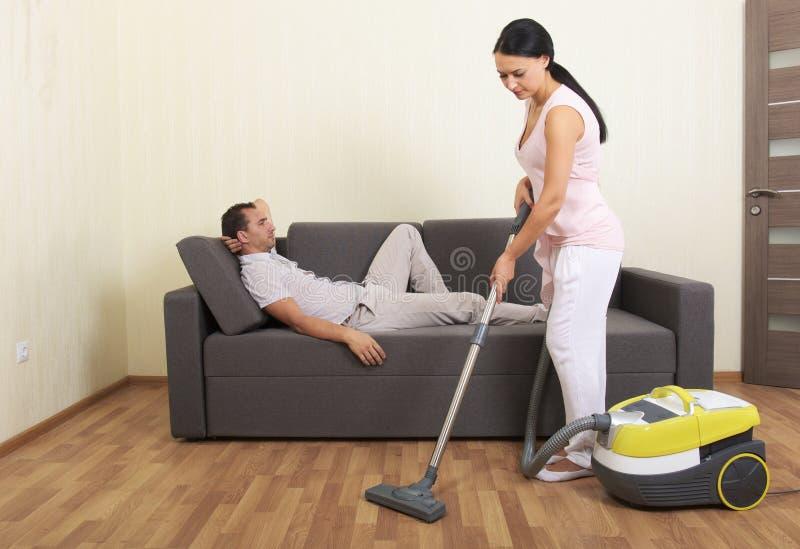 Mujer que limpia con la aspiradora y hombre de reclinación imagen de archivo